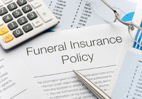 Close up of approved funeral insurance policy with pen, calculator